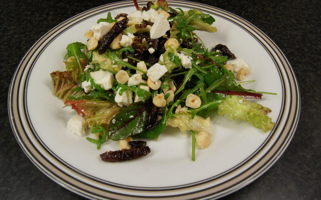 Salade met gedroogde pruimen, feta en hazelnoten