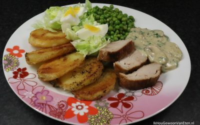 Gebakken aardappels, erwtjes, sla en varkenshaas met champignonroomsaus